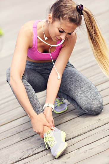 Female athlete runner touching ankle injury in pain