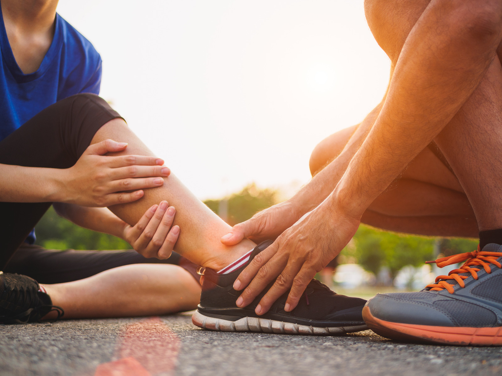 Ankle Sprain Injury. Young woman suffering from an ankle injury while exercising and running and she getting help from man touching her ankle.